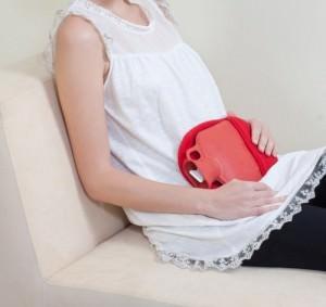 женщина сидит с грелкой на животе