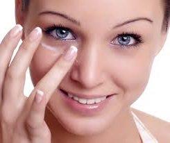 женщина кладет крем вокруг правого глаза