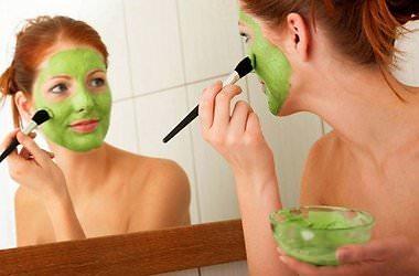 женщина наносит маску из глины зеленого цвета на лицо