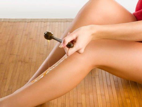 женщина делает шугаринг на левой ноге