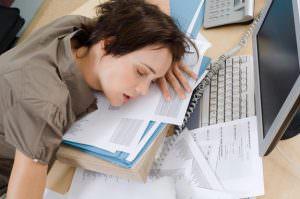 девушка спит на книгах возле компьютера