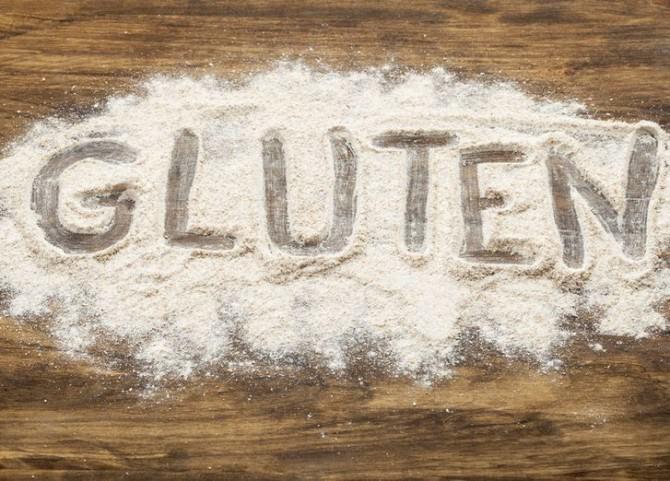 На столе рассыпана мука и на ней написано слово gluten